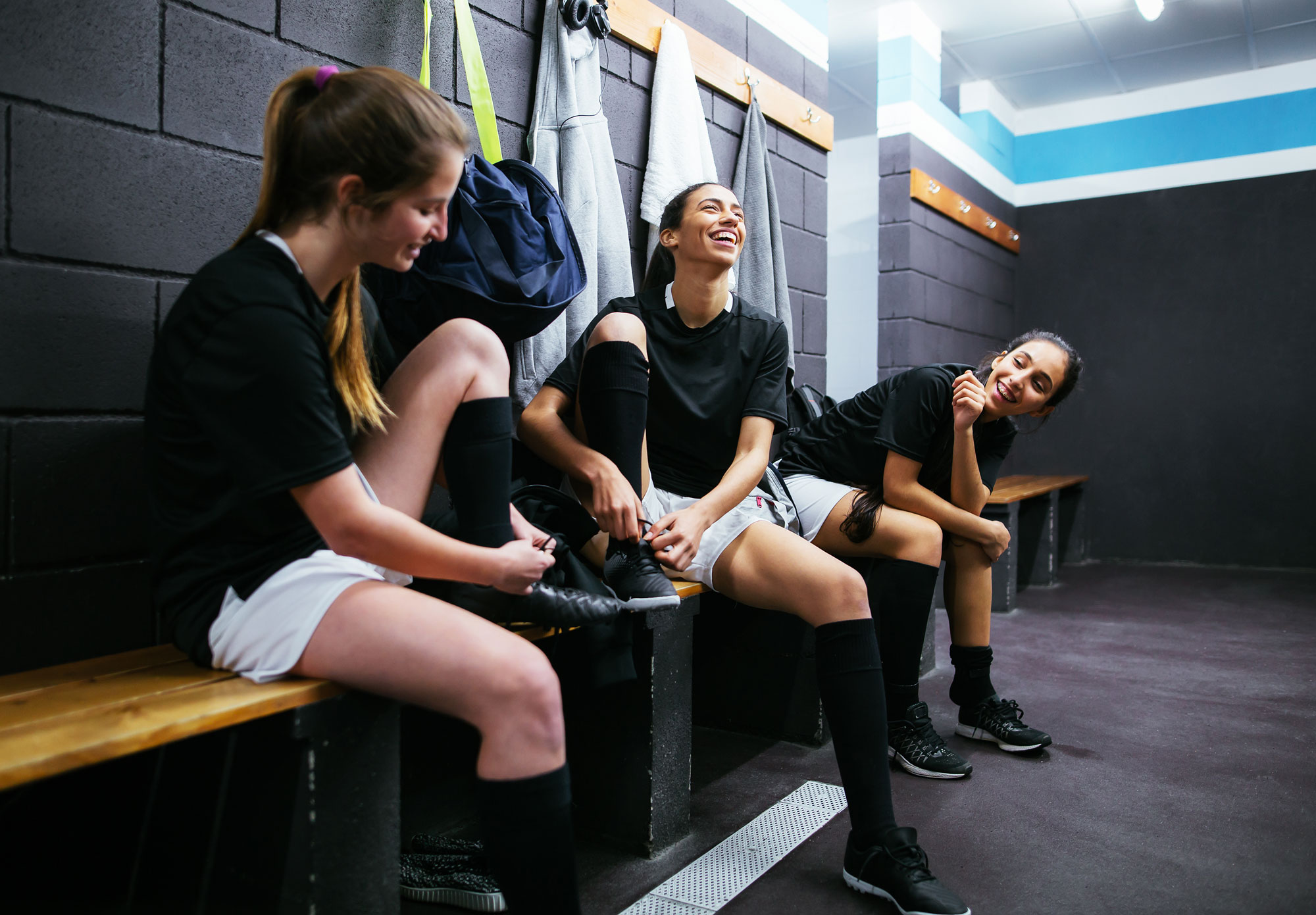Three young athletes lacing up their shoes in the locker room