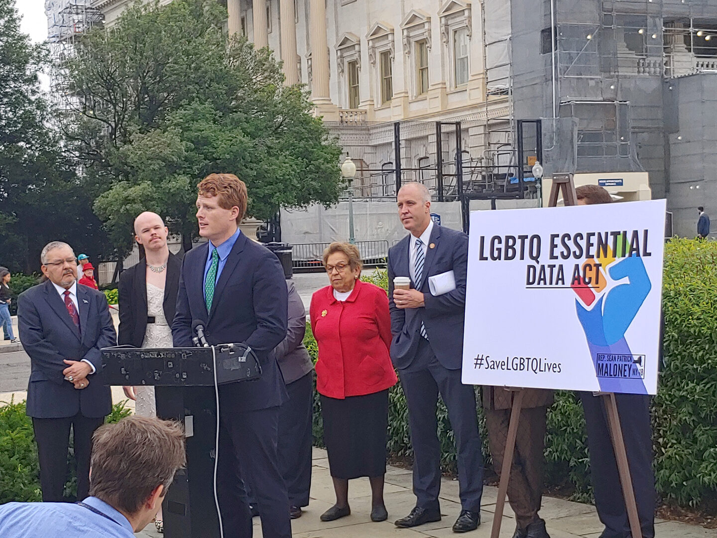 """A group of people standing behind a podium, where Representative Maloney is addressing a crowd. A sign next to him reads, """"LGBTQ Essential Data Act."""""""