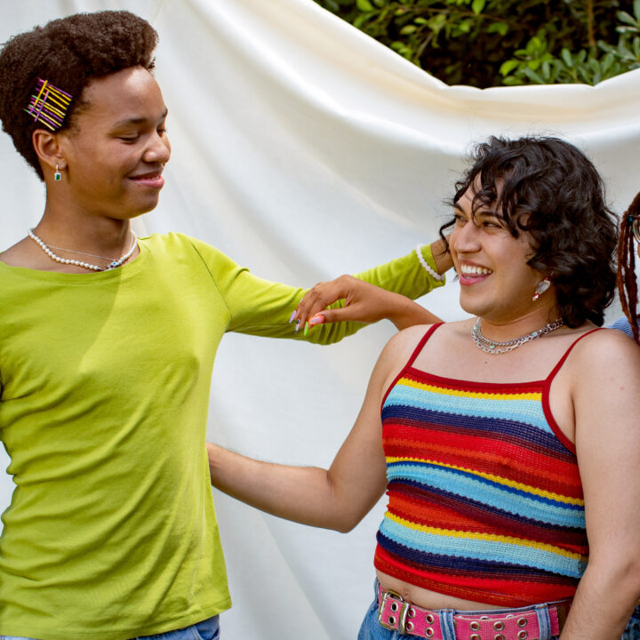 LGBTQ young people going in to hug each other and smiling