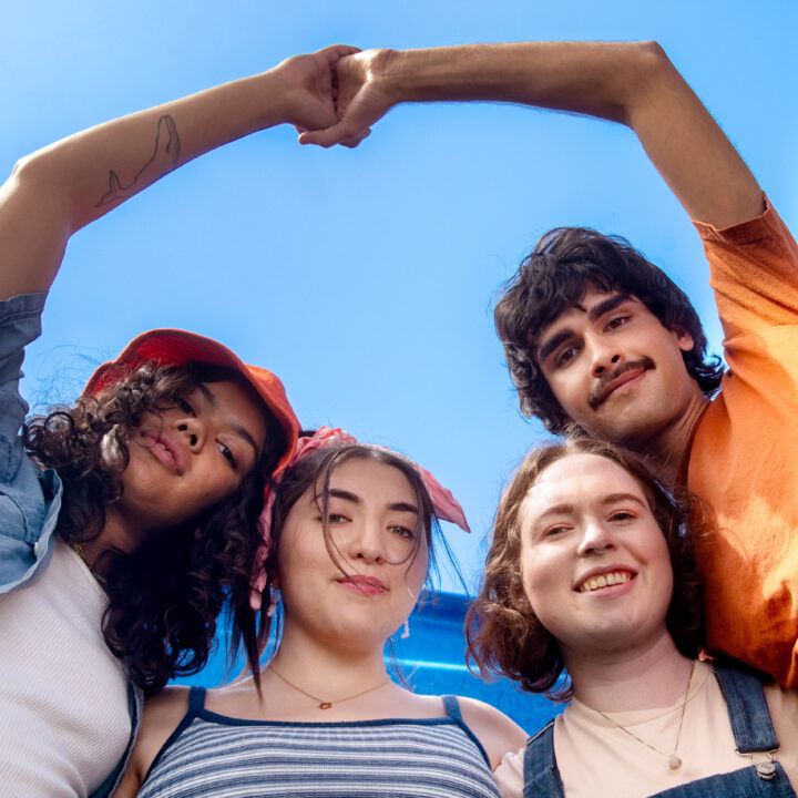 Group of LGBTQ youth, smiling and with their arms around each other, photographed from below with the sky behind them