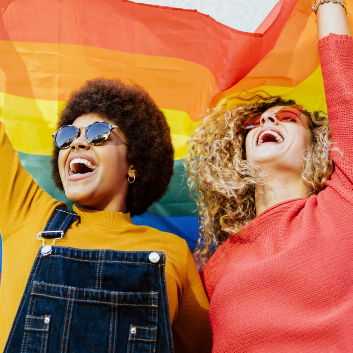 Two people celebrating under a pride flag.