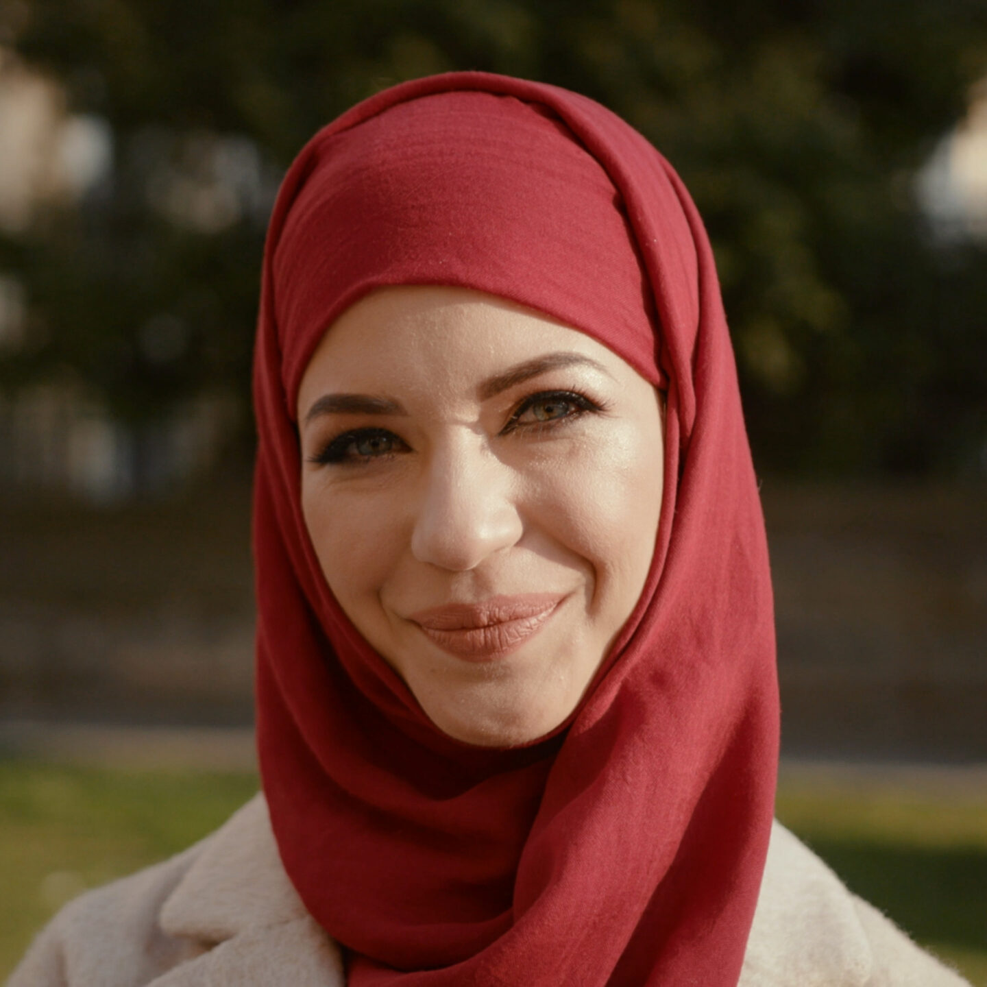 Person wearing a red hijab smiling.