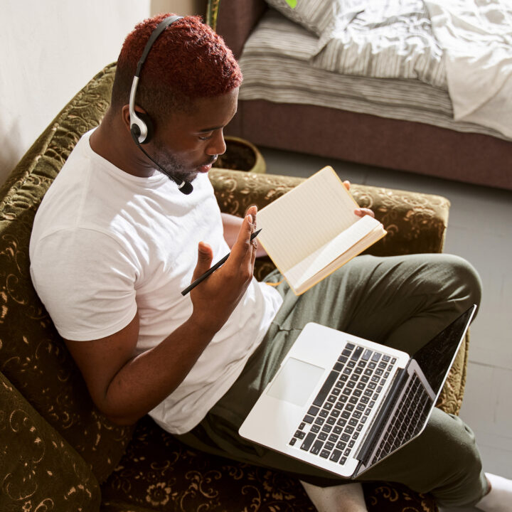Person attending webinar on their laptop in their home.