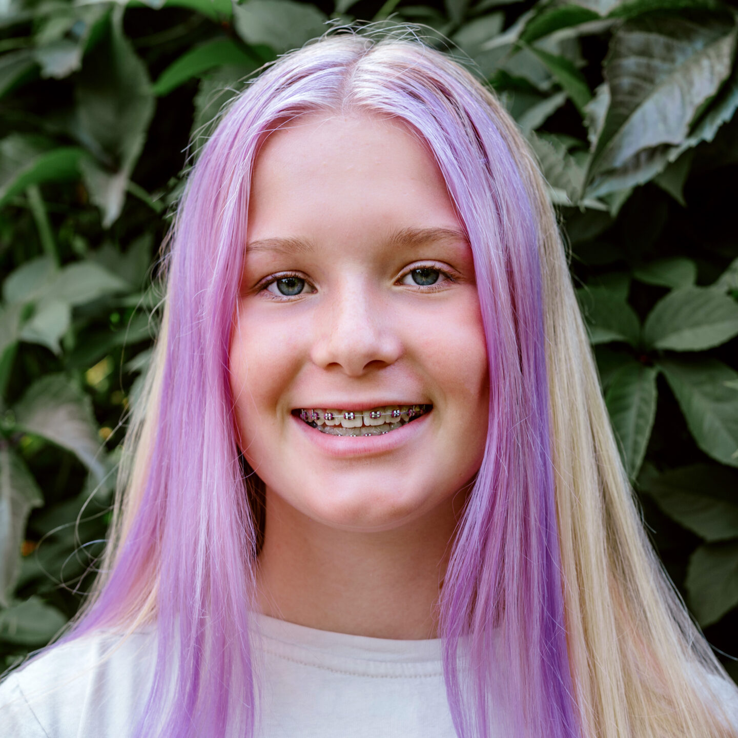 LGBTQ young person with braces smiling.