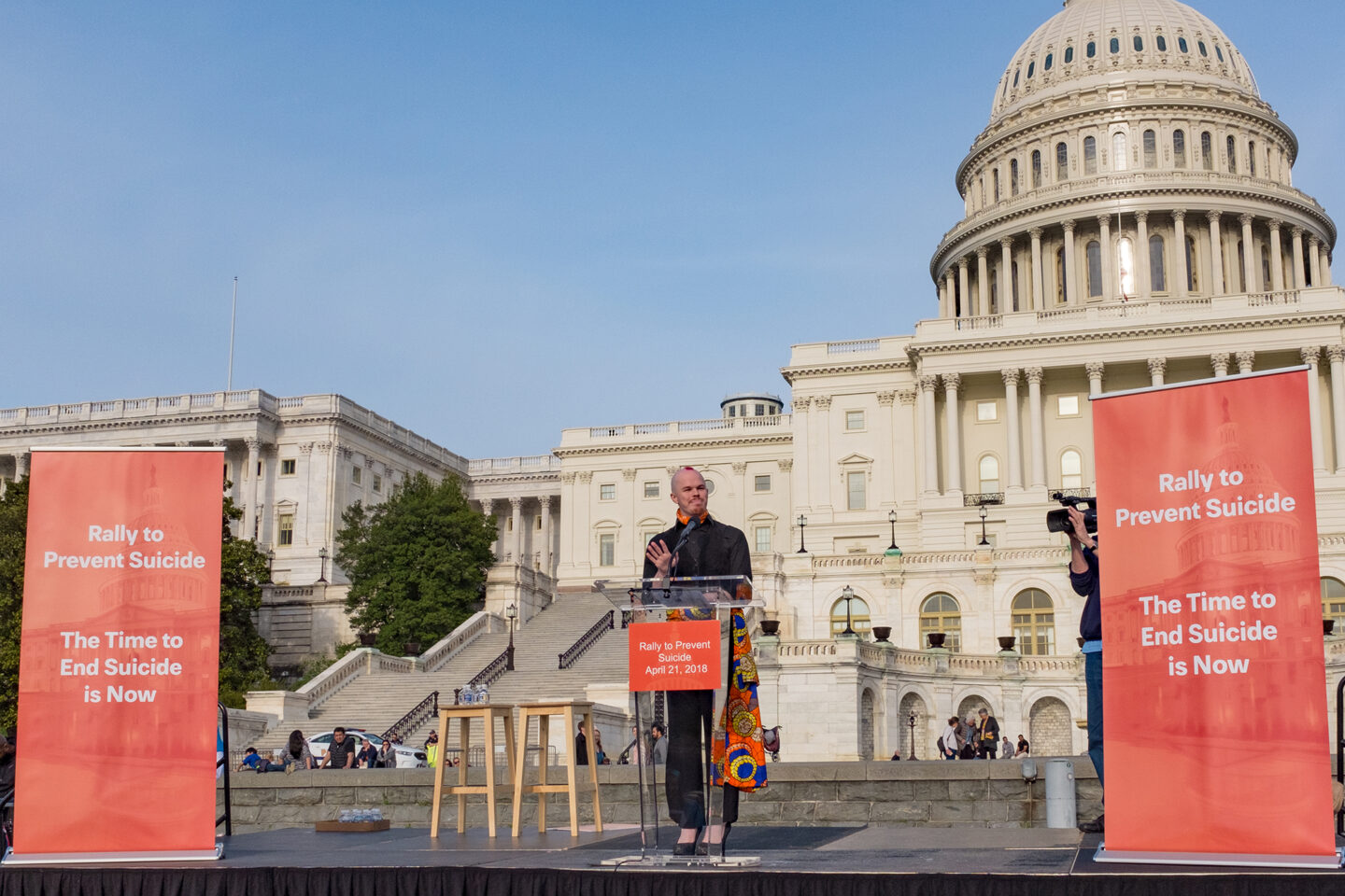 """Sam speaks to a crowd in front of the Capitol Building in Washington, D.C. They stand between two large orange signs that say, """"Rally To Prevent Suicide, The Time to End Suicide is Now."""""""