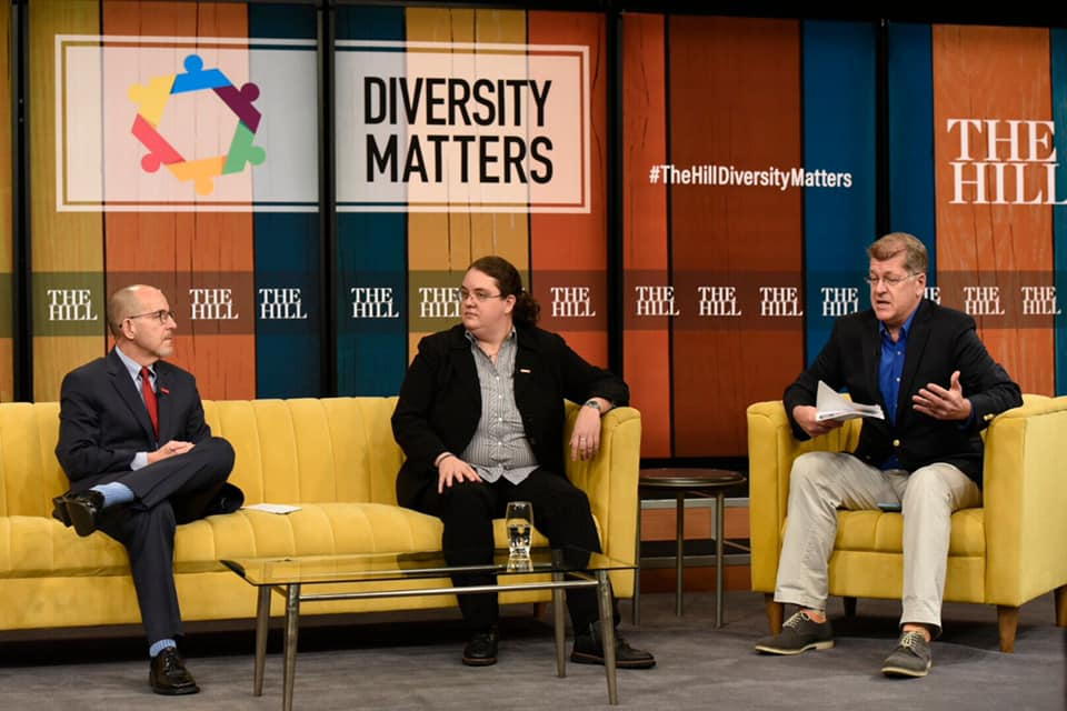 Casey sits on a yellow couch in conversation with two other people, beneath a Diversity Matters sign.