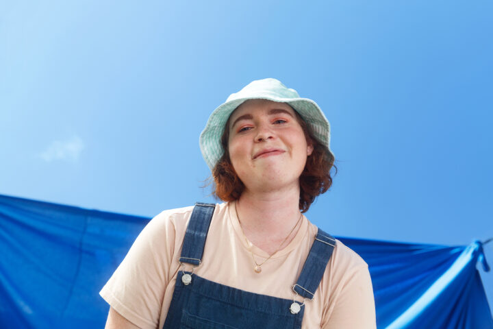 Portrait of LGBTQ youth smiling at the camera with a blue sky background