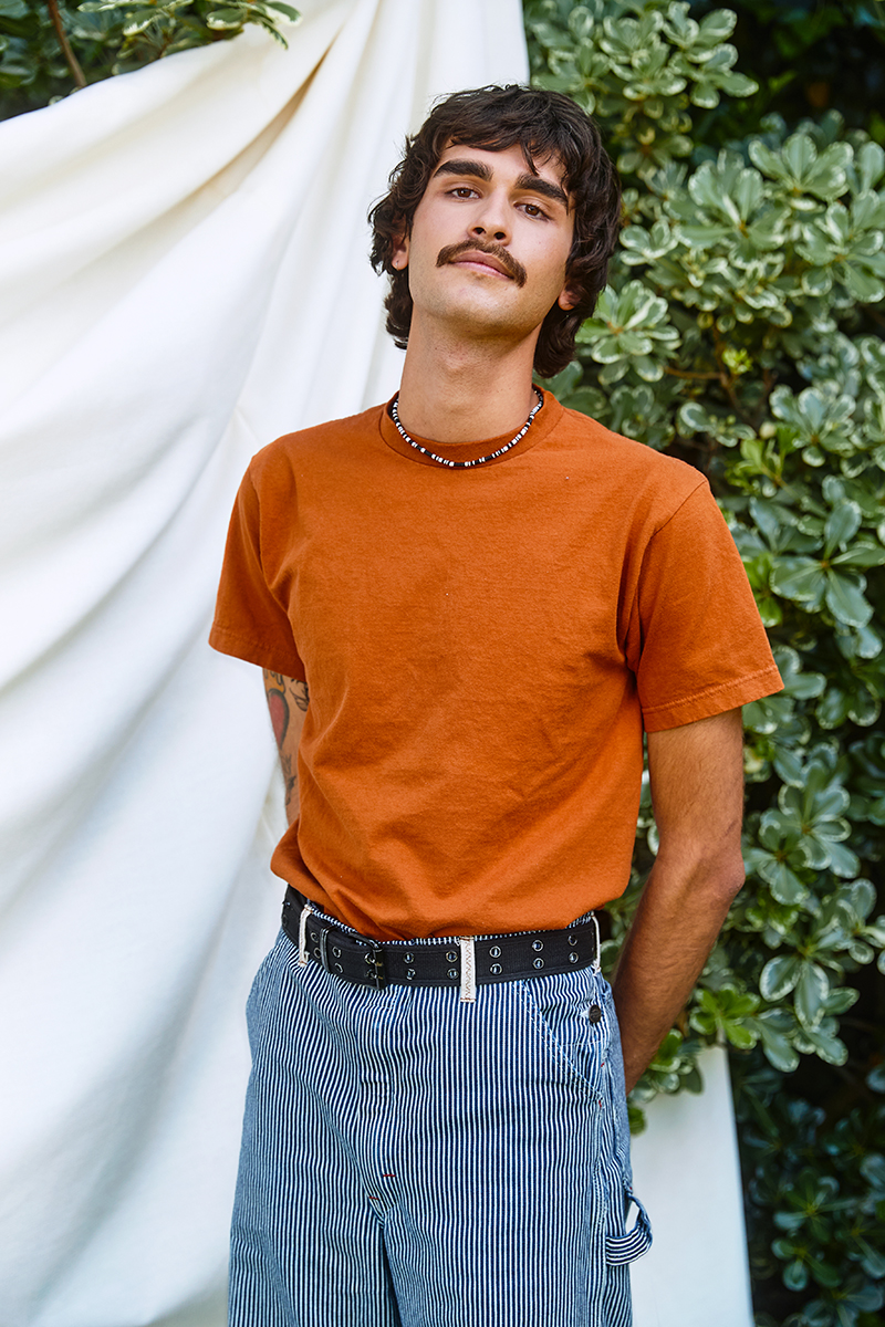 Portrait of a LGBTQ young person wearing an orange shirt with a white backdrop