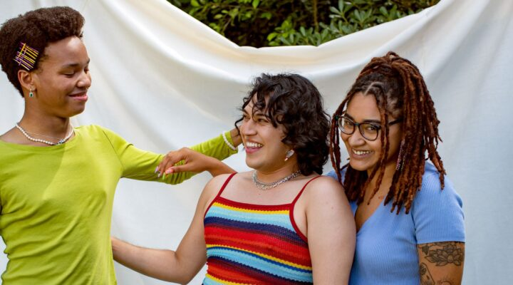 LGBTQ young people smiling and hugging each other