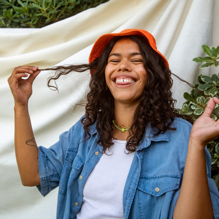 Young person laughing, standing outside in front of a neutral fabric backdrop