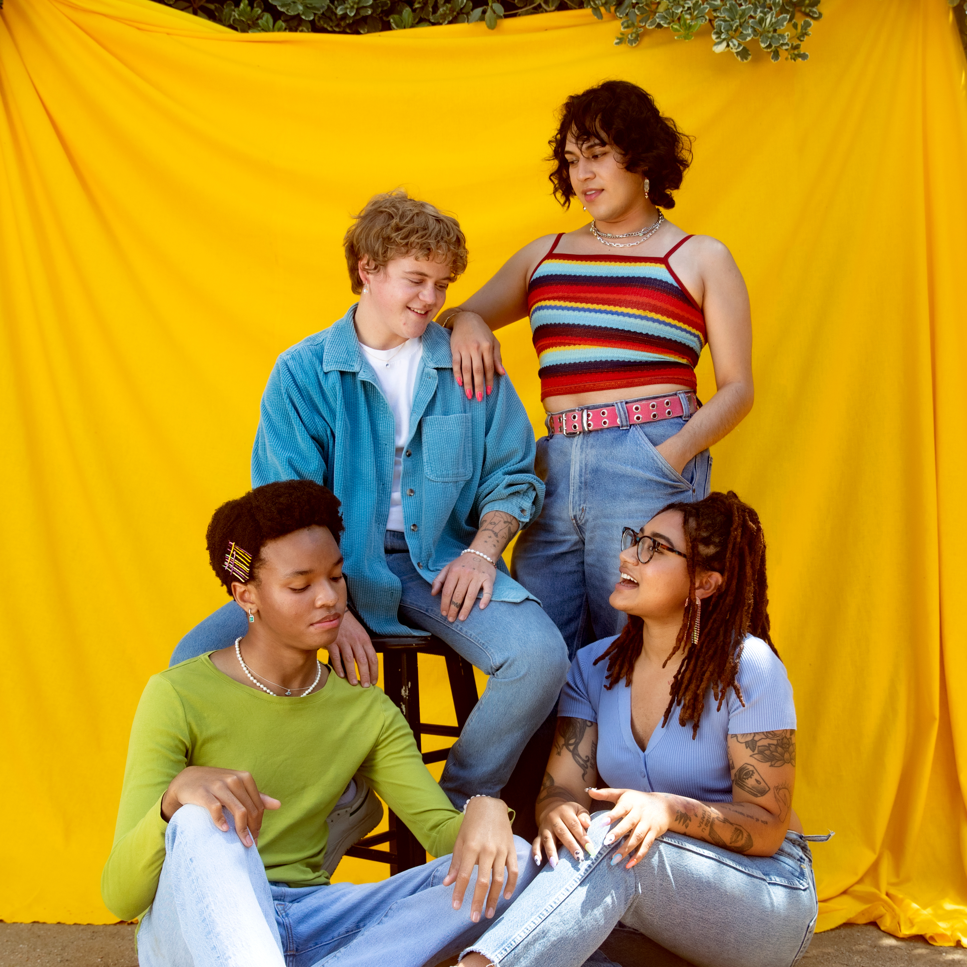 Four young people in colorful clothing standing against a yellow backdrop talking.