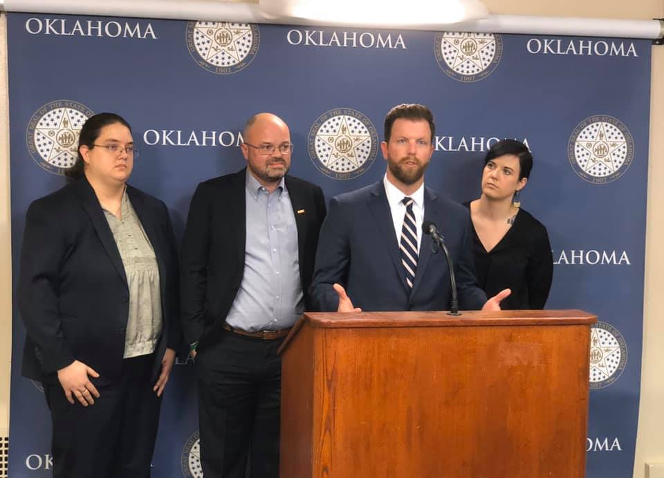 Three people stand behind Representative Jason Dunnington as he speaks at a podium.