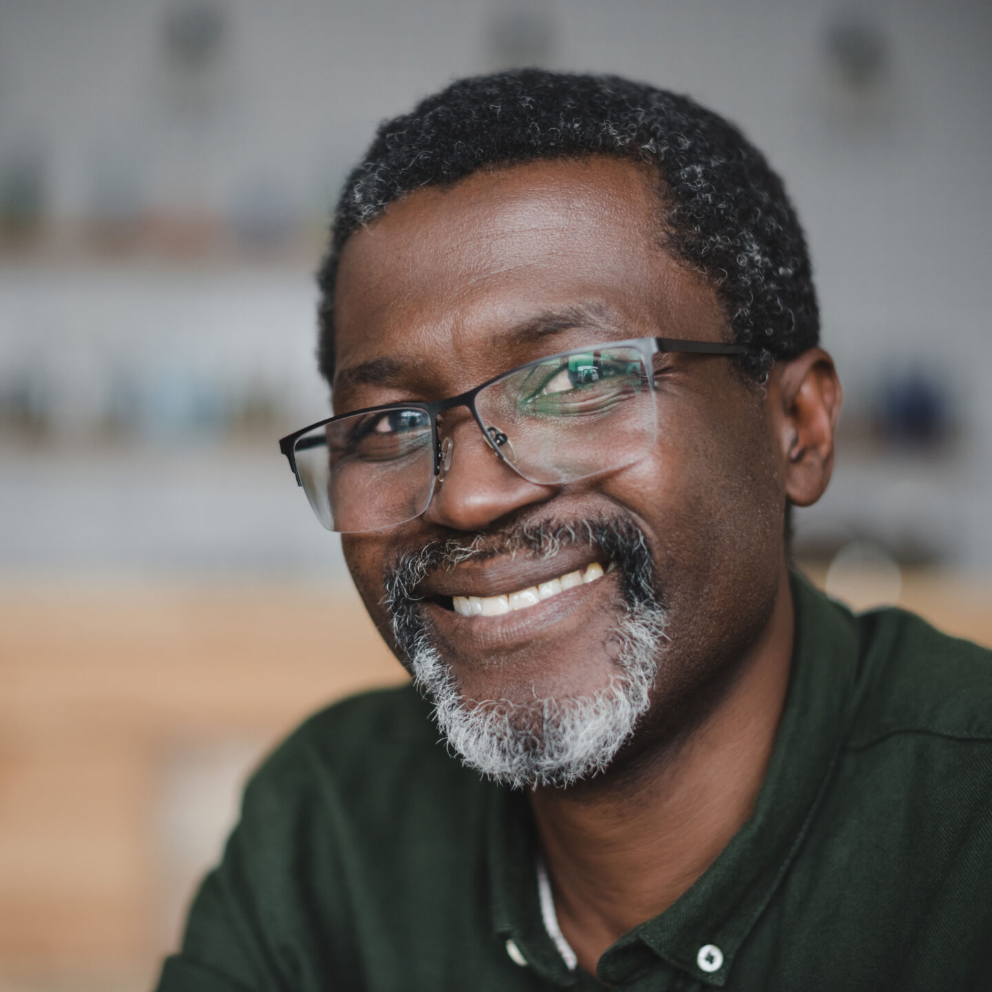 An adult with a grey beard and glasses smiling in their home.
