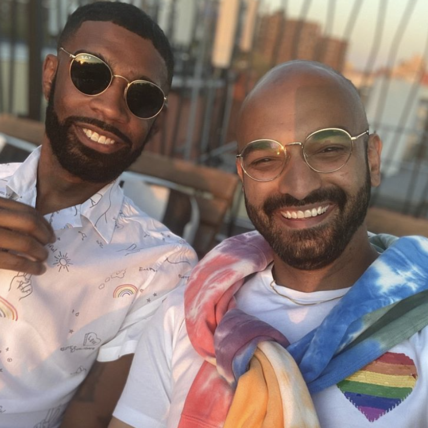 Two smiling people wearing rainbow pride attire on a rooftop at sunset.